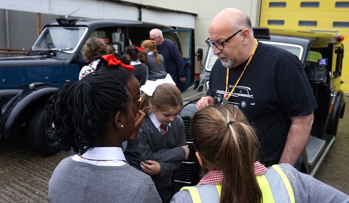 London Vintage Taxi Association mebers show children some old London taxis